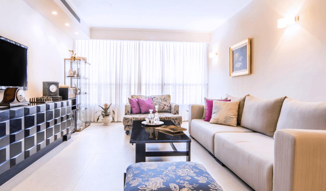 סלון דירה ברעננה עם שידת עץ גיאומטרית, וספות מרופדות בדירה ברעננה - שירית דרמן עיוב פנים ותכנון תאורה