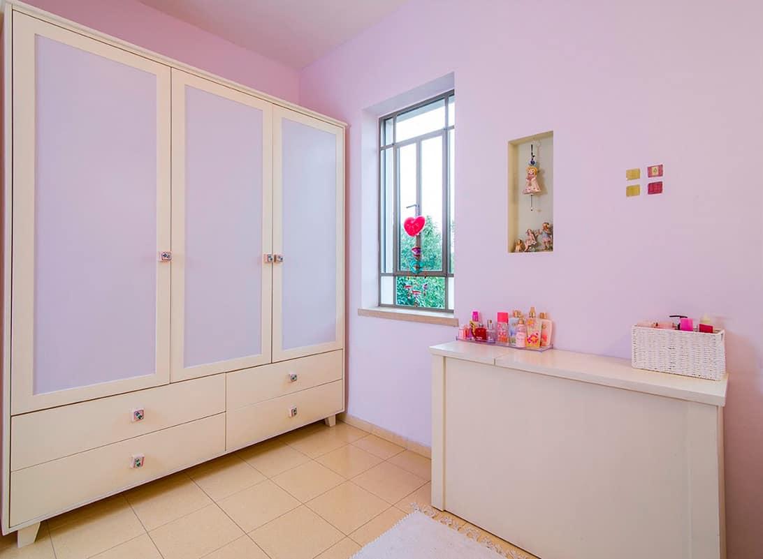 ארון עץ בצבע שמנת עם חזיתות בצבע סגול בהיר בחדר של נערה בבית פרטי בעמק חפר - שירית דרמן מעצבת פנים