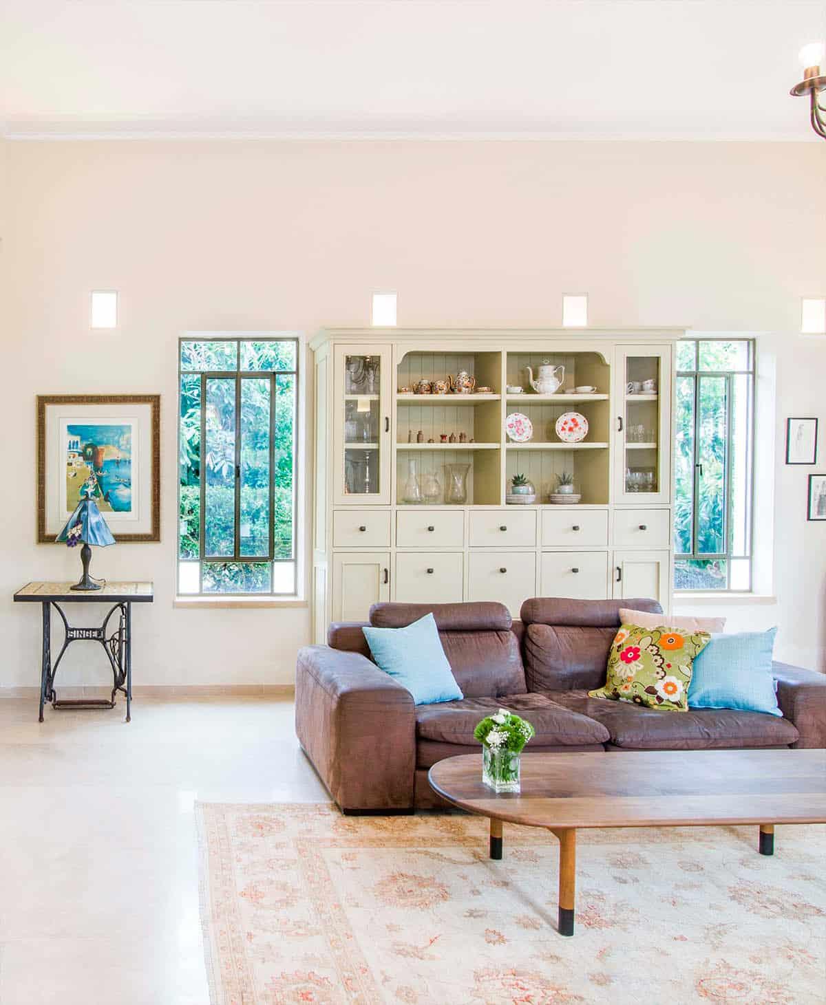 ספרייה בצבע פיסטוק הניצבת בין שני חלונות בבית פרטי בעמק חפר - שירית דרמן, מעצבת פנים ויועצת תאורה