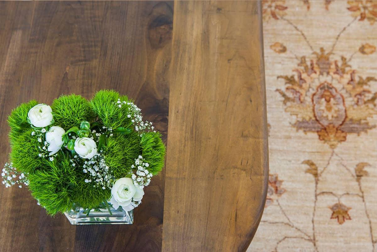 סידור פרחים בלבן וירוק על רקע שולחן עץ ושטיח זיגלר - שירית דרמן מעצבת פנים