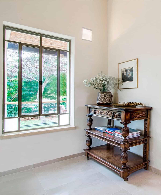 שידת עץ עתיקה מגולפת וטבע ירוק הנשקף מחלון בית פרטי בעמק חבר, בעיצובה של מעצבת הפנים, שירית דרמן