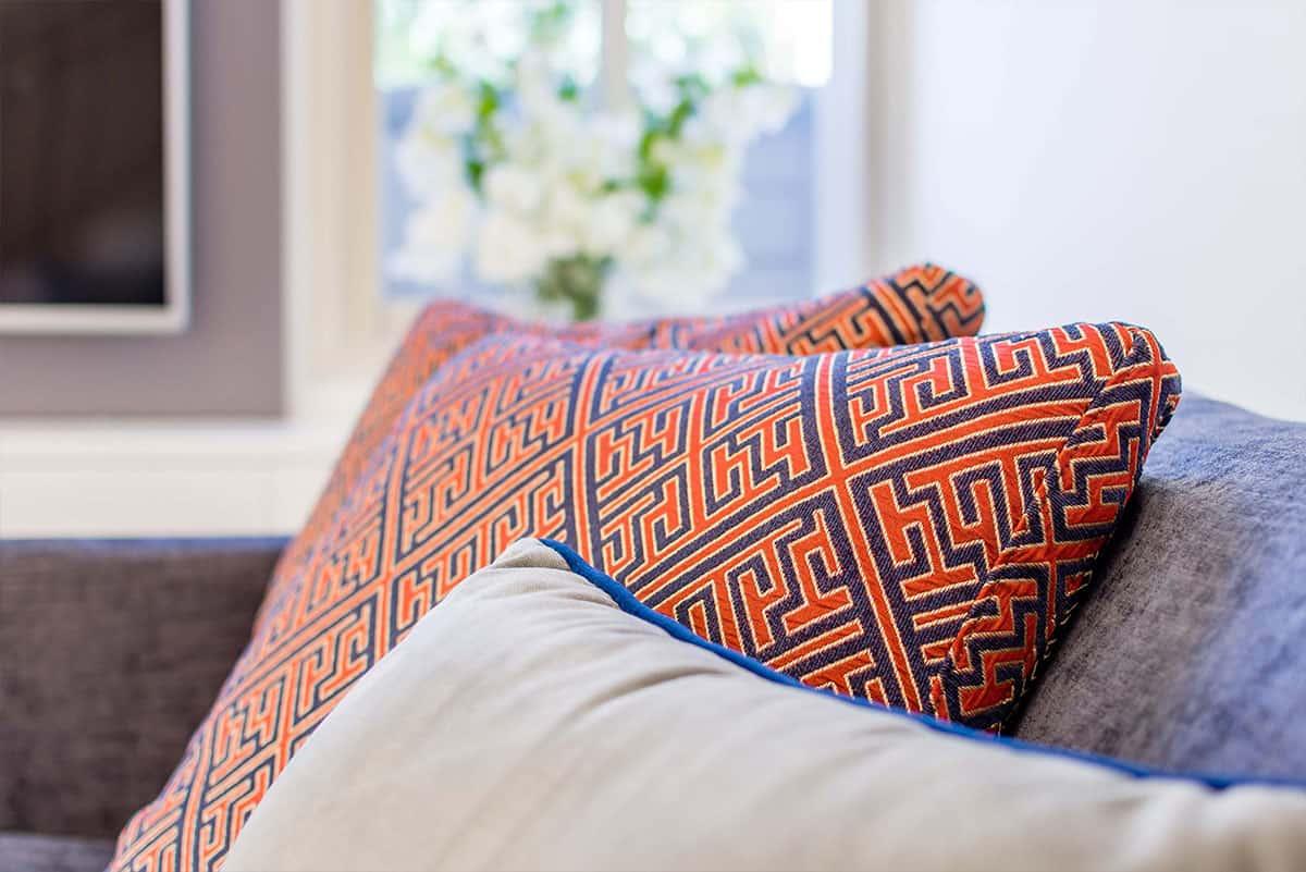 כריות שונות מקטיפה ועם הדפסים גאומטריים על ספת הסלון - שירית דרמן מעצבת פנים