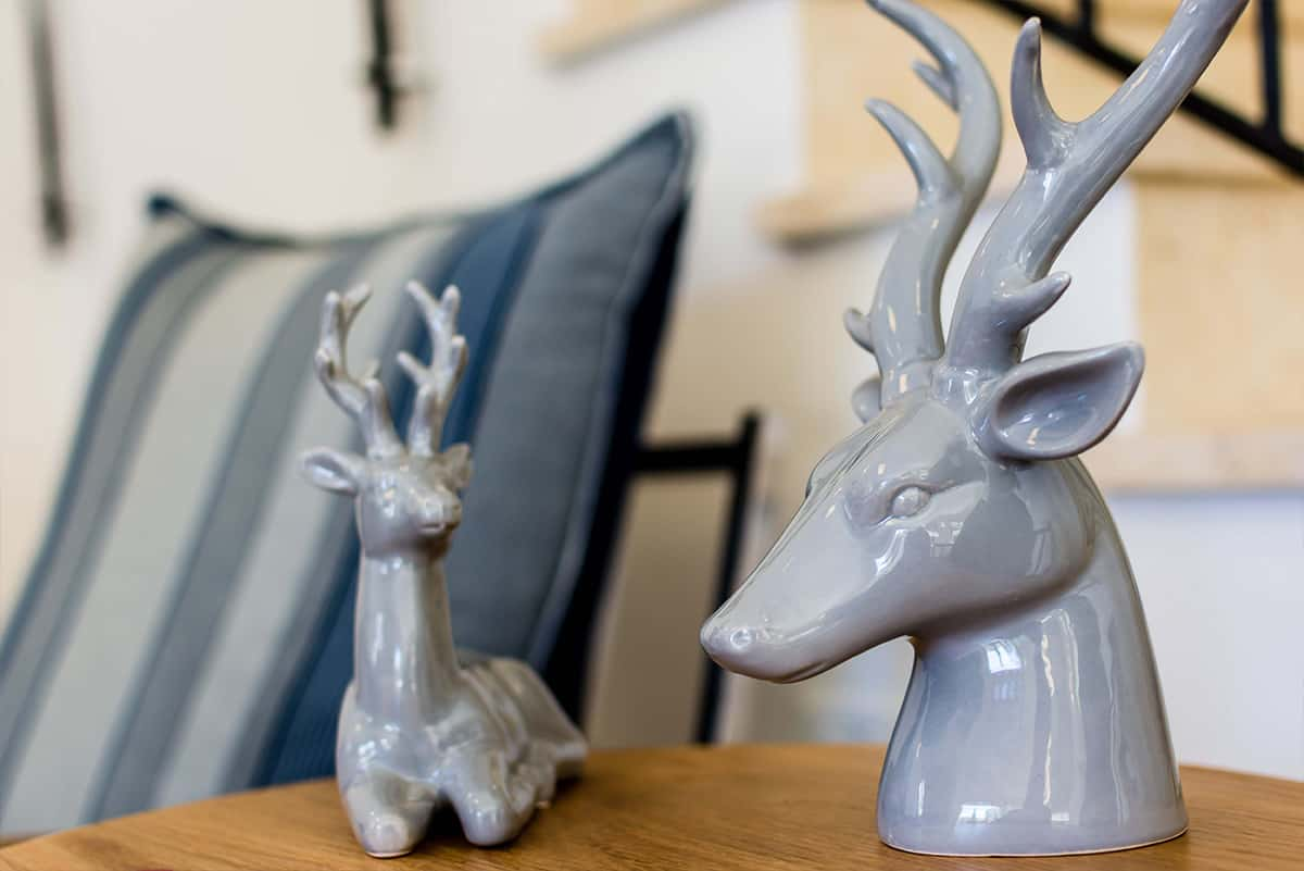 פסלי איילים אפורים מקרמיקה על שידת הסלון בבית פרטי באבן יהודה - שירית דרמן מעצבת פנים