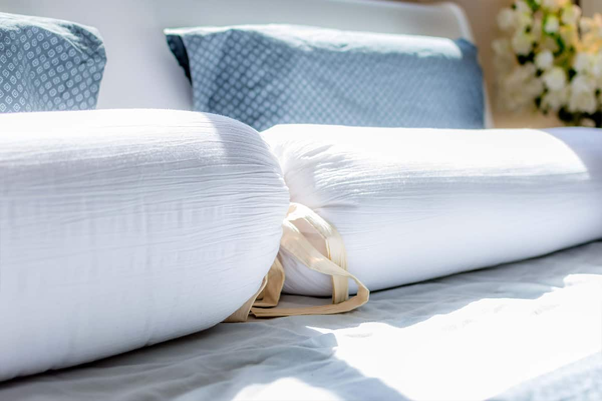 קרני אור השמש על כריות המיטה בחדר שינה בבית פרטי באבן יהודה, שעוצב על ידי שירית דרמן