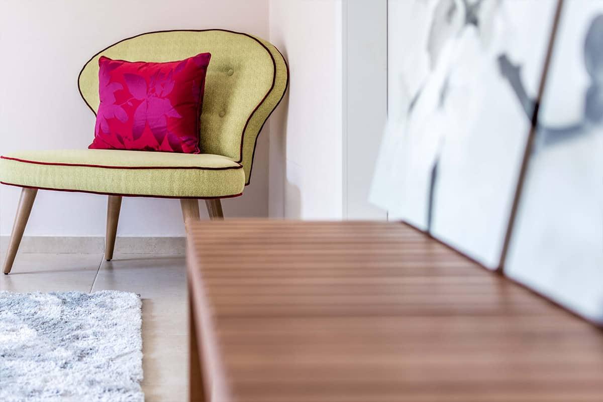 כורסת קפיטונאז' במראה רטרו וספסל עץ עם תמונות בחדר שינה בבית פרטי באבן יהודה - שירית דרמן מעצבת פנים