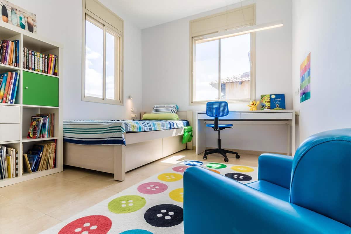 חדר ילדים גדול ומואר עם מנורה מלבנית תלויה לאורכו של שולחן הכתיבה בבית פרטי באבן יהודה - שירית דרמן מעצבת פנים ויועצת תאורה