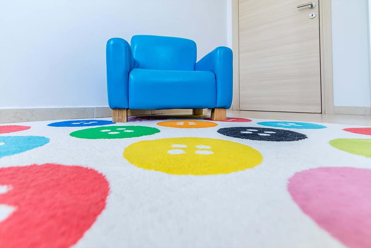 שטיח עם דוגמת כפתורים וכורסת ילדים כחולה - שירית דרמן מעצבת פנים