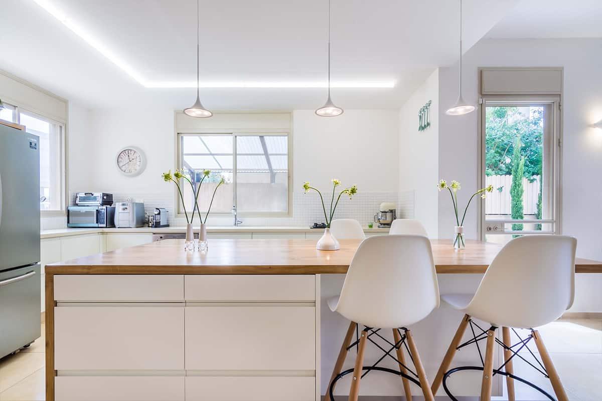 שלושה גופי תאורה במראה עכשווי תלויים מעל האי במטבח בבית פרטי באבן יהודה - שירית דרמן עיצוב פנים ותכנון תאורה