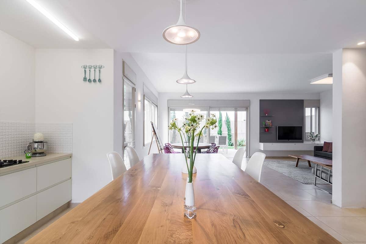 מבט אל משטח העץ של האי במטבח והסלון הפתוח בבית פרטי ומואר באבן יהודה - שירית דרמן עיצוב פנים ותכנון תאורה