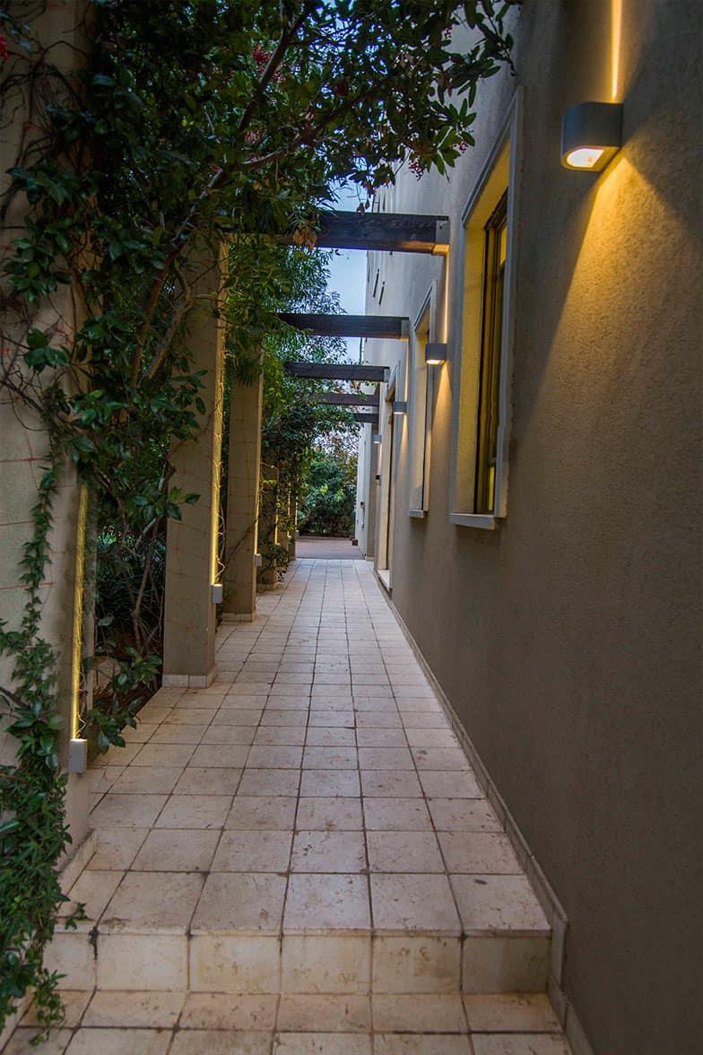 שביל כניסה צר ומואר משני צידיו - עיצוב ותכנון תאורה שירית דרמן