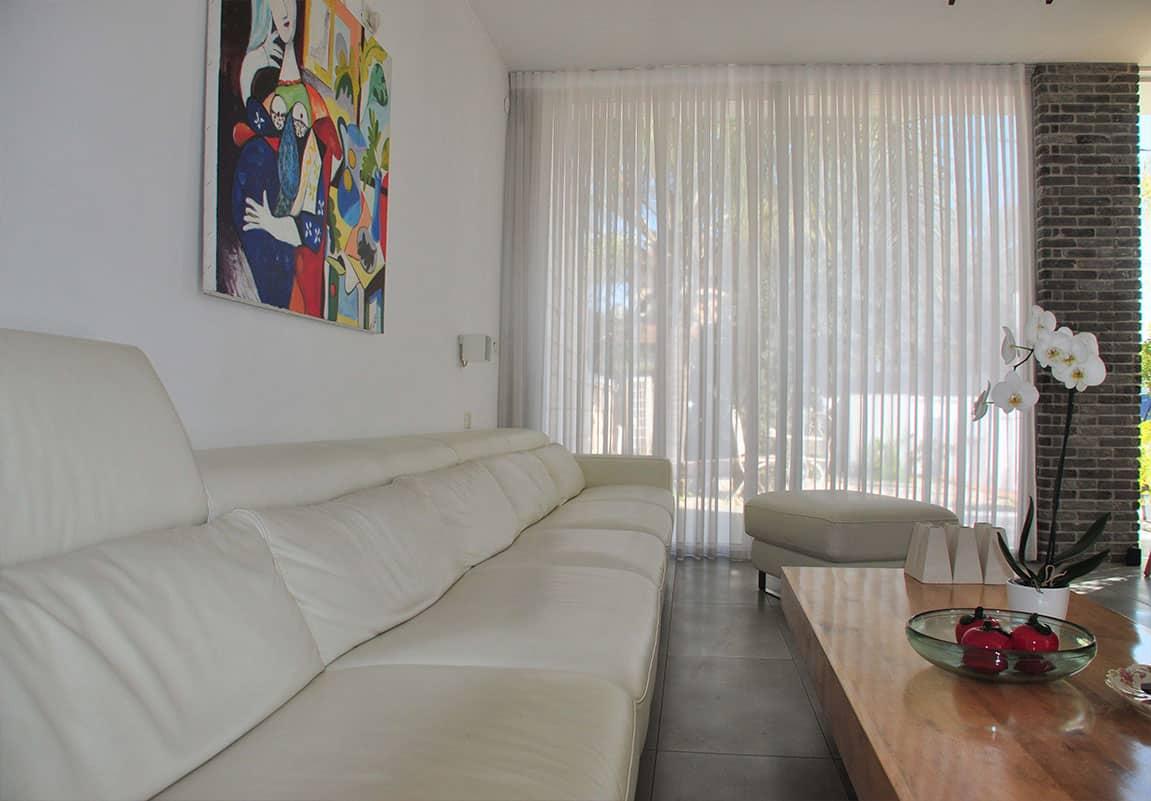 ספה לבנה ארוכה ווילון לבן בסלון בית פרטי בהוד השרון - שירית דרמן מעצבת פנים
