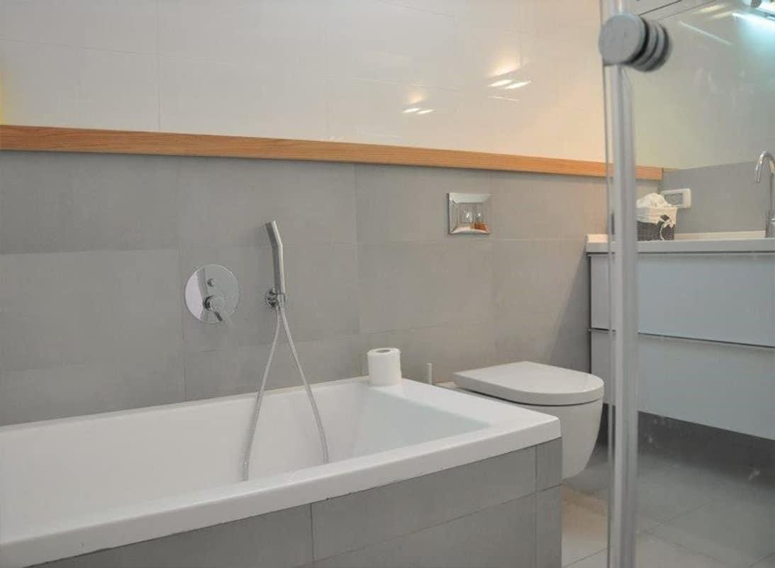 חדר רחצה עם אריחים מלבניים אפורים ומדף עץ ארוך - שירית דרמן מעצבת פנים