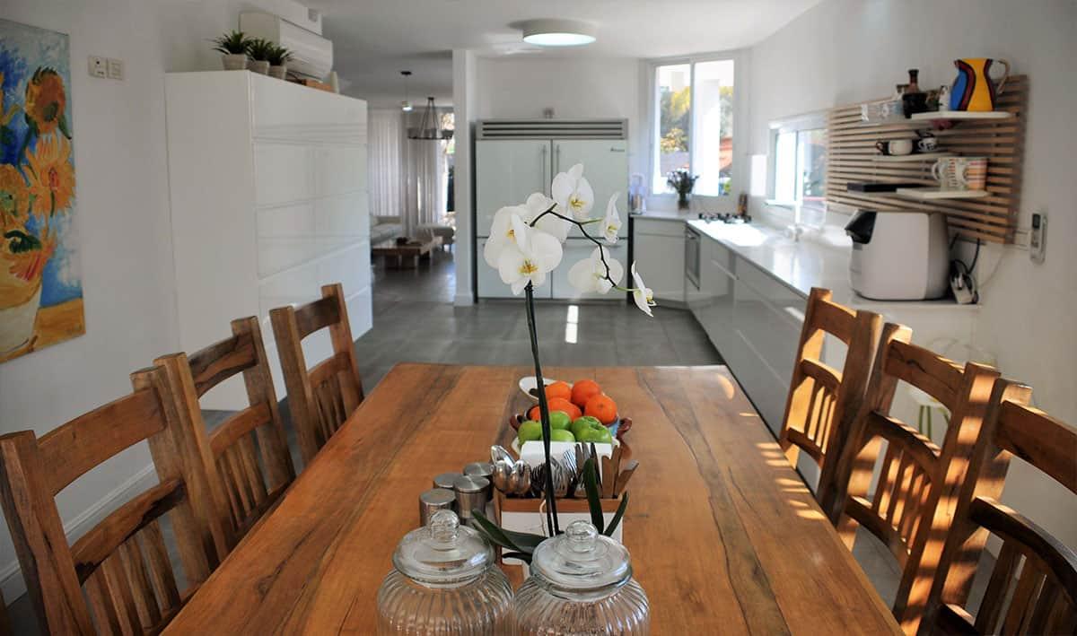מטבח בהיר עם שולחן עץ גושני בבית פרטי בהוד השרון - שירית דרמן מעצבת פנים