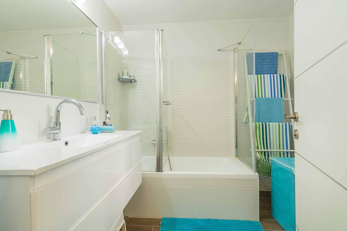 חדר רחצה בדירה בעיר ימים עם אריחי רצפה דמויי פרקט וקירות מחופים באריחים לבנים תלת מימדיים - שירית דרמן מעצבת פנים ויועצת תאורה