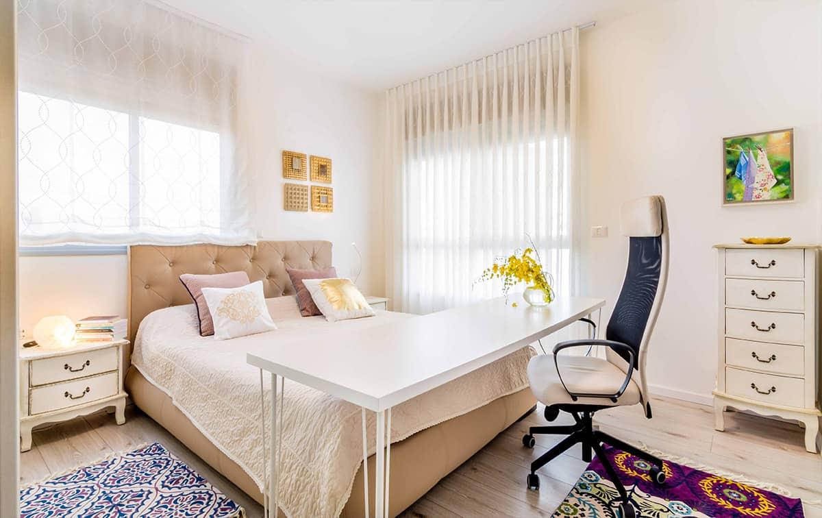 חדר שינה בדירה בעיר ימים עם שטיחים רקומים ושולחן נייד המשמש לעבודה - עיצוב פנים שירית דרמן