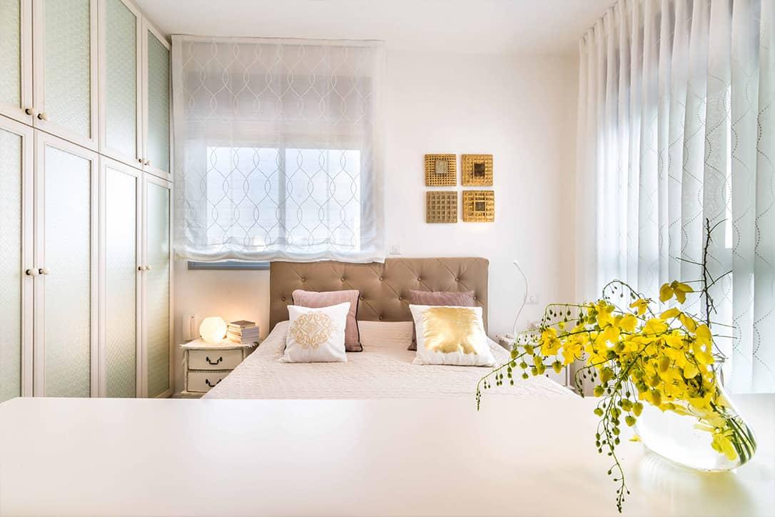 וילונות לבנים רקומים בחדר שינה בעיר ימים עם מיטת קפיטונאז' שעליה כריות - שירית דרמן מעצבת פנים