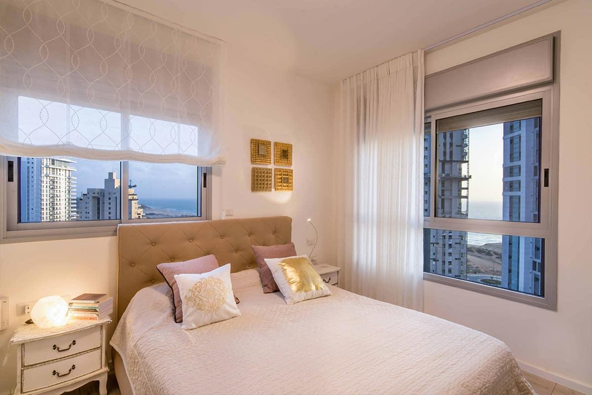 חדר שינה בדירה בעיר ימים עם שני חלונות גדולים המשקיפים אל הים - שירית דרמן מעצבת פנים ויועצת תאורה