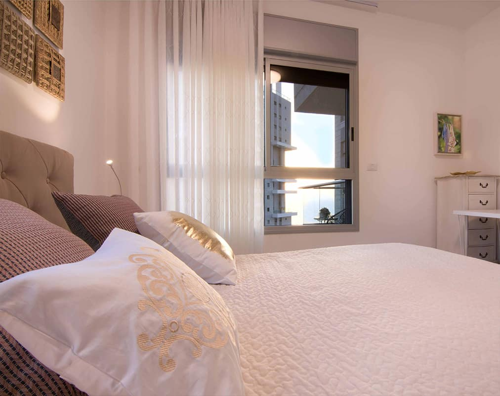 מיטת קפיטונאז' שעליה כיסוי מיטה רקום בחדר שינה בדירה בעיר ימים - שירית דרמן מעצבת פנים