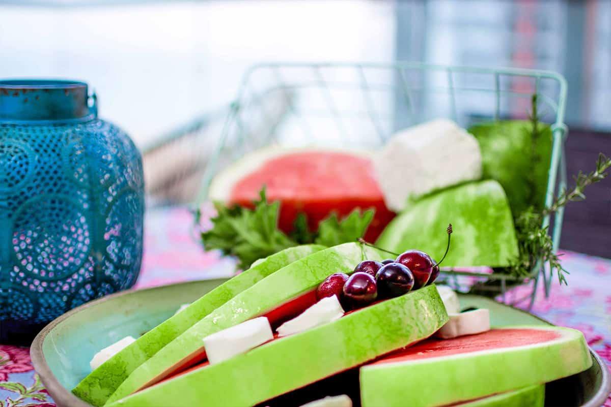פלחי אבטיח צוננים, גבינה בולגרית ודובדבנים לצד עששית בצבע טורקיז, על מרפסת דירה בעיר ימים - שירית דרמן עיצוב פנים