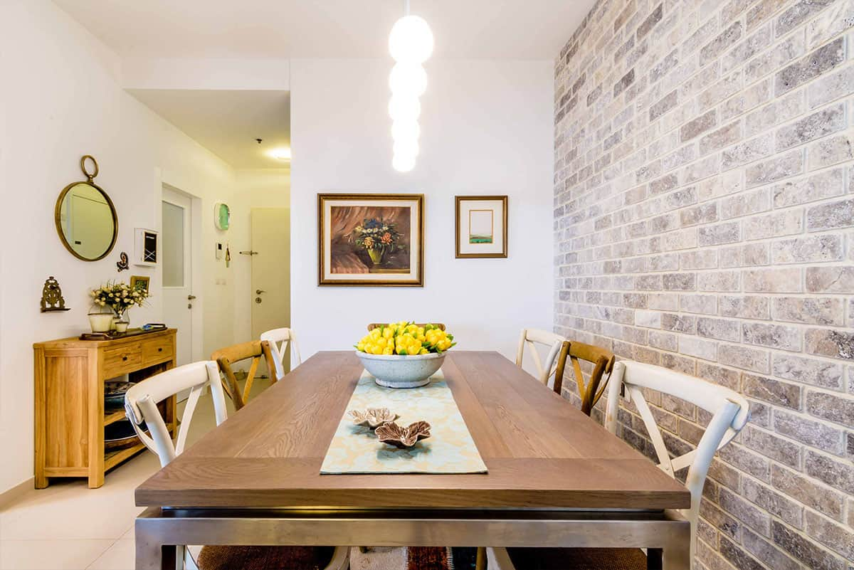 שולחן פינת האוכל בדירה בעיר ימים עם כיסאות עץ קלועים בצבע טבעי ובצבע לבן - שירית דרמן עיצוב פנים ותכנון תאורה