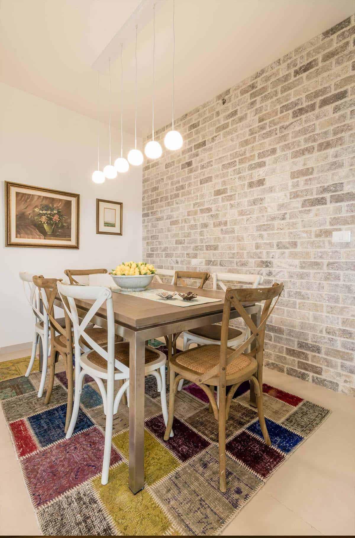 כיסאות עץ קלועים בפינת אוכל שעל שטיח טלאים צבעוני - שירית דרמן עיצוב פנים ותכנון תאורה