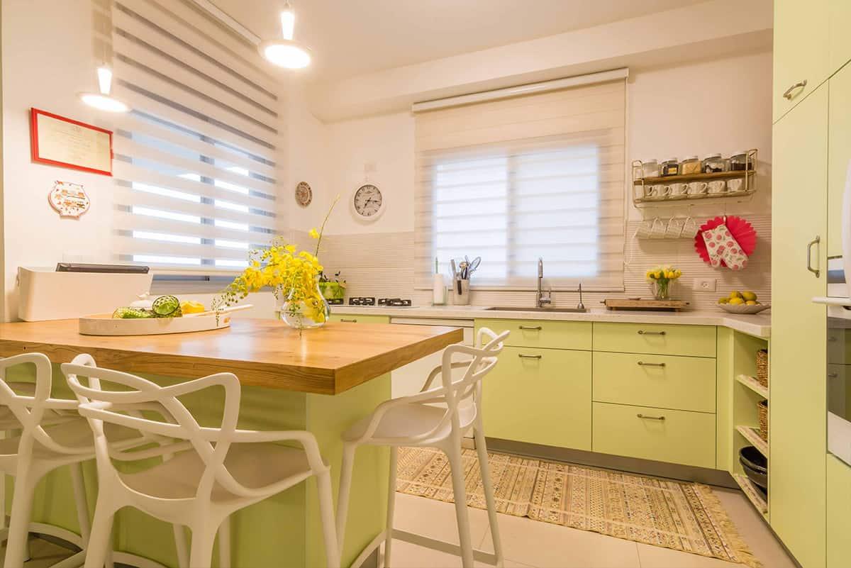 מטבח בצבע ירוק פיסטוק בהיר עם משטח אכילה מעץ בדירה בעיר ימים - תכנון ועיצוב פנים שירית דרמן