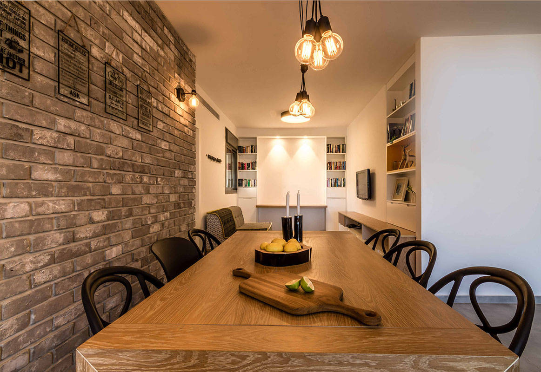פינת האוכל מוארת בנורות פחם לצד קיר בריקים אפור בדירה בכפר סבא הירוקה - שירית דרמן עיצוב פנים ותכנון תאורה