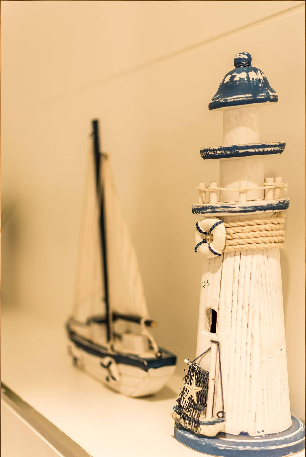 פריטי עיצוב של סירת מפרש ומגדלור מעץ לבן בחדר רחצה בכפר סבא הירוקה - שירית דרמן מעצבת פנים