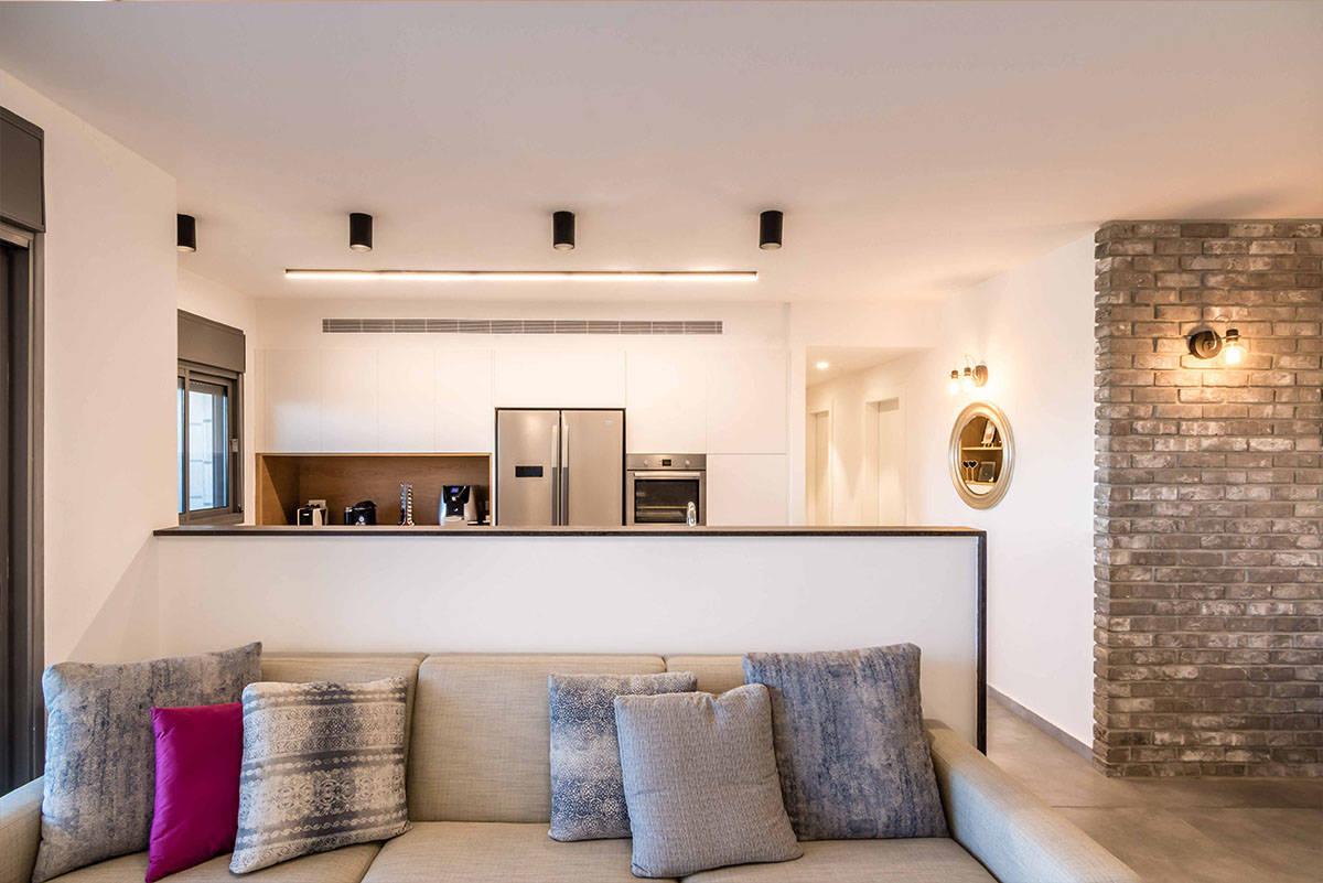 הפרדה חלקית של המטבח יוצרת פתיחות של המטבח ליתר החלל הציבורי בדירה בכפר סבא הירוקה - עיצוב ותכנון - שירית דרמן מעצבת פנים
