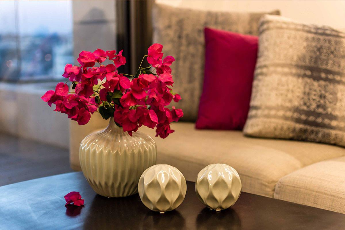 פרחי בוגנווויליה ורודים על רקע ספה בהירה - שירית דרמן מעצבת פנים