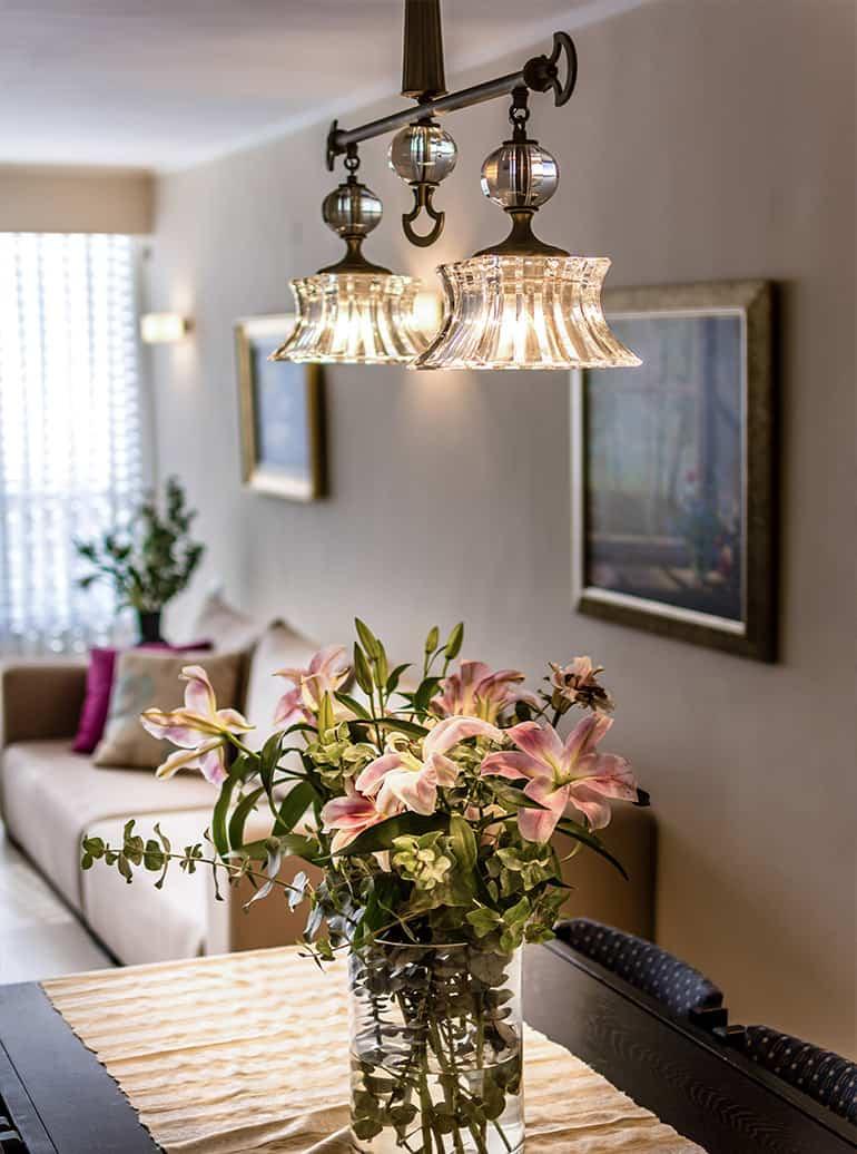 גוף התאורה בפינת אוכל בדירה ברעננה מאיר את סידור הפרחים - שירית דרמן מעצבת פנים ויועצת תאורה -