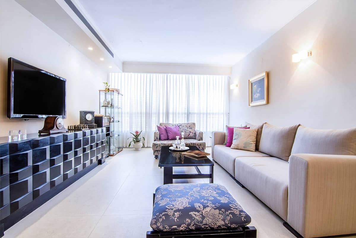 סלון דירה ברעננה עם שידת עץ גיאומטרית, וספות מרופדות באריגים צבעו - עיצוב פנים שירית דרמן