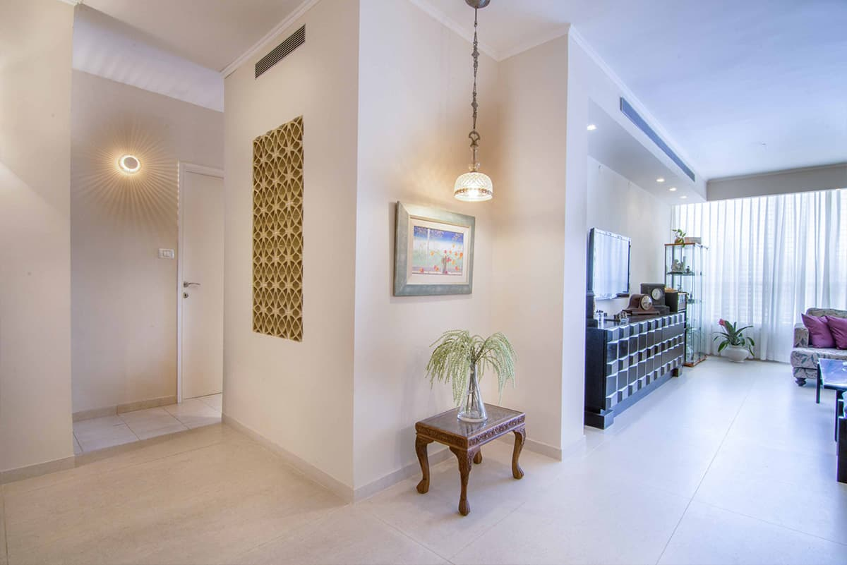 מגוון גופי תאורה לצד קיר משרביות החוצץ בין החלל הציבורי לפרטי בדירה בעיצובה של שירית דרמן מעצבת פנים ויועצת תאורה