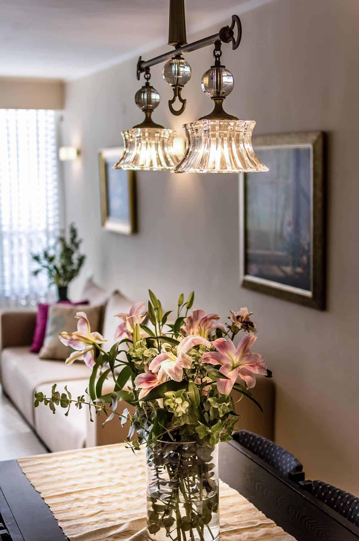 נברשת קריסטל מודרנית ואגרטל פרחים ססגוני על שולחן פינת אוכל בדירה ברעננה - שירית דרמן מעצבת פנים ויועצת תאורה