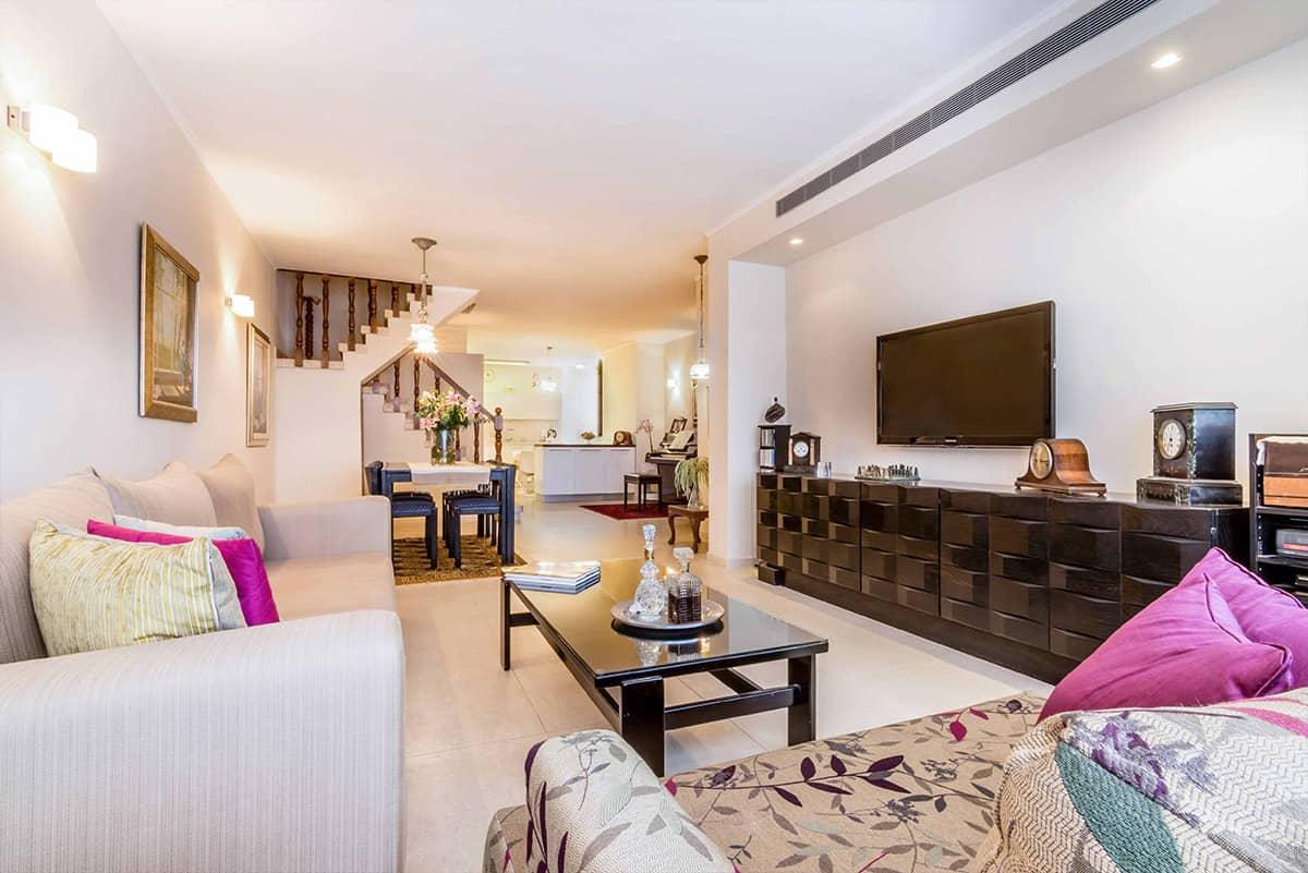 מבט עומק אל הסלון, פינת האוכל, גרם המדרגות והמטבח בדירה ברעננה - שירית דרמן מעצבת פנים