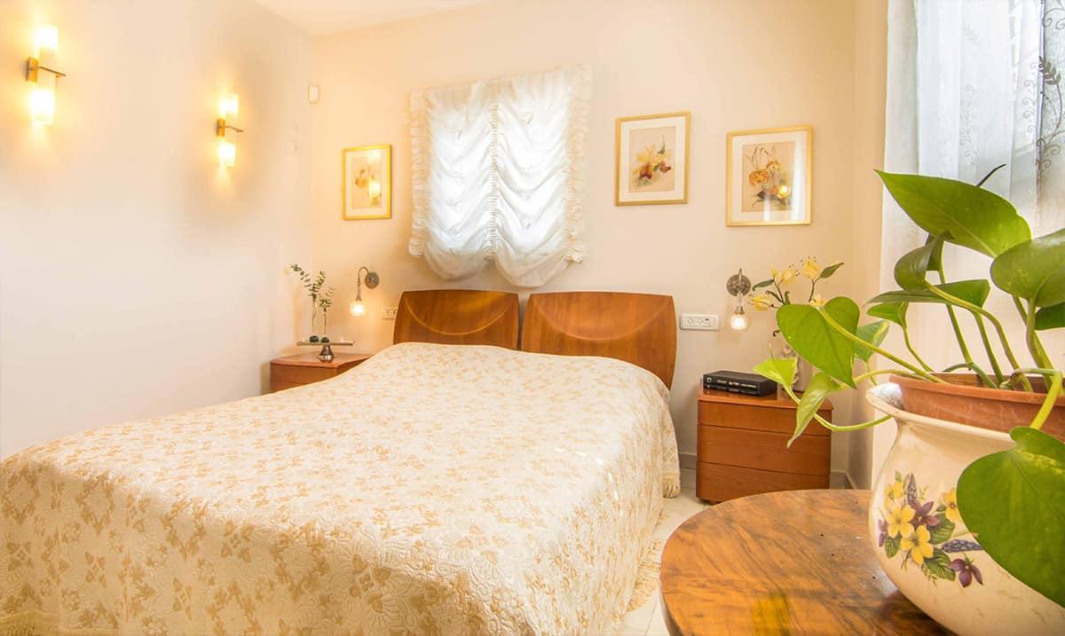 חדר שינה ברעננה, עם רהיטי עץ בסגנון קלאסי, מנורות קיר וכיסוי מיטה מבד אנגלי רקום - שירית דרמן מעצבת פנים