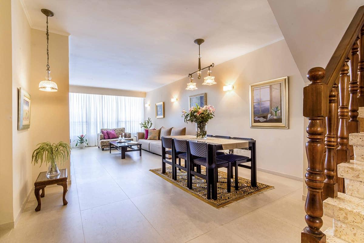 פינת האוכל והסלון בדירה ברעננה המוארת בגופי תאורה צמודי קיר וגם נברשות קריסטל מודרני תלויות מהתקרה - שירית דרמן מעצבת פנים ויועצת תאורה