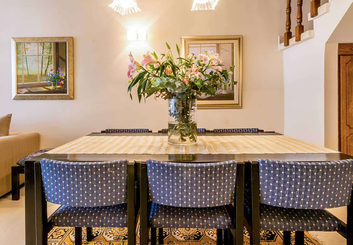 פינת אוכל עם כיסאות מרופדים בבד כחול מודפס, סידור פרחים על שולחן האוכל ויצירות אנות שתלויות על הקיר - שירית דרמן מעצבת פנים ויועצת תאורה