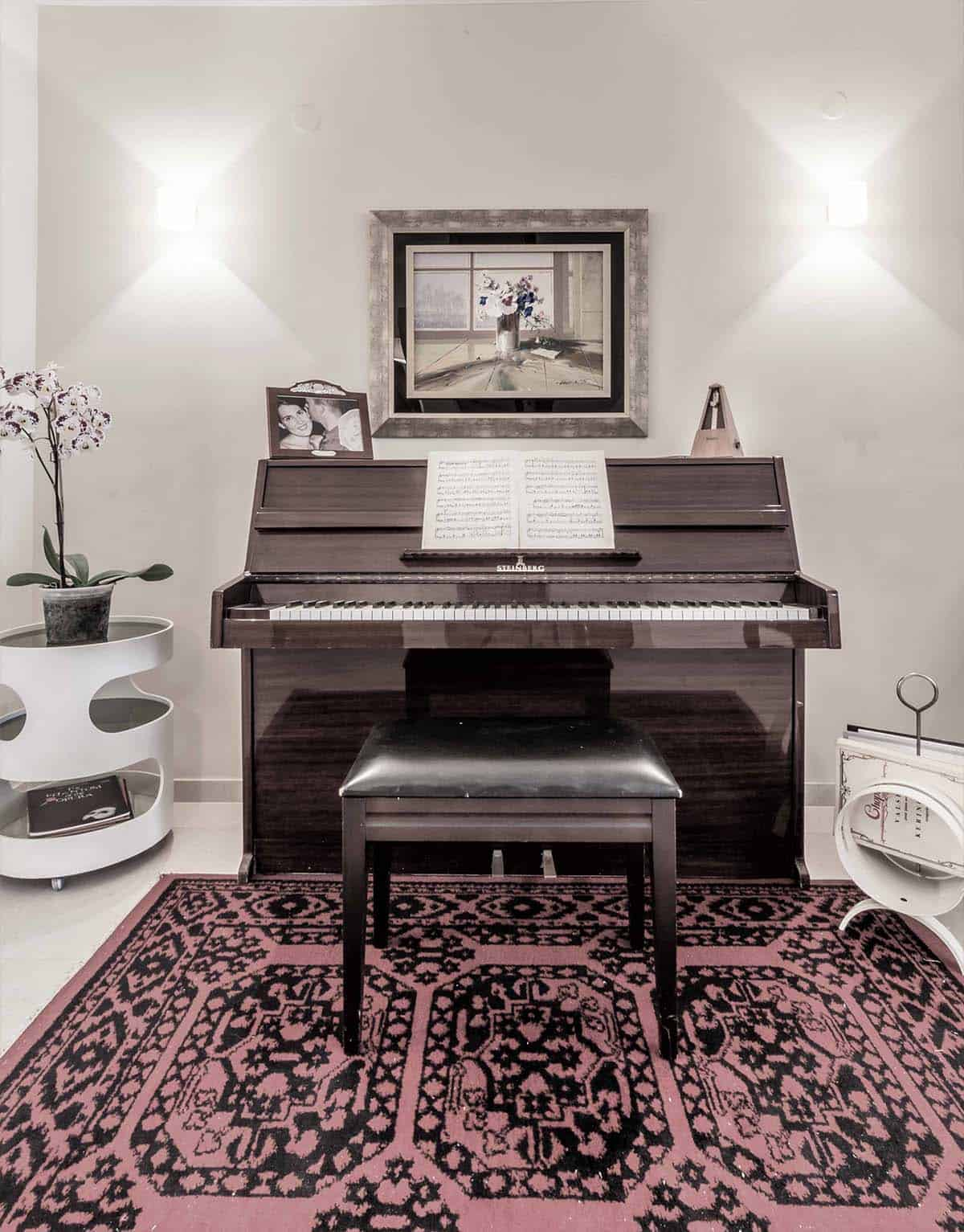 פסנתר בדירה ברעננה המואר משני צידיו במנורות קיר המפזרות אלומות אור למעלה ולמטה - שירית דרמן מעצבת פנים ויועצת תאורה