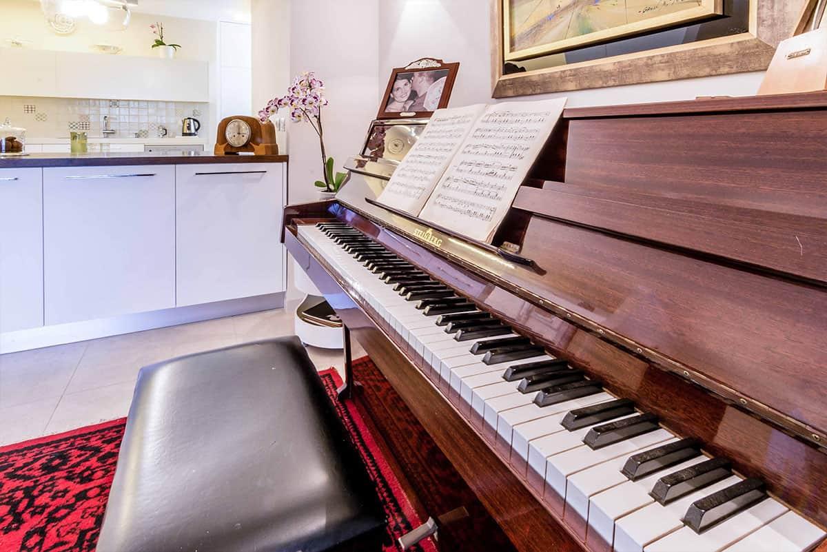 פסנתר מבהיק עליו מונח ספר תווים וברקע נגרות לבנה של המטבח - שירית דרמן מעצבת פנים
