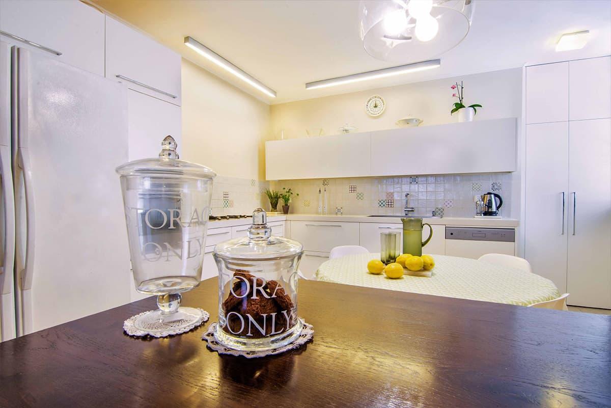 משטח עץ מלא במטבח בדירה ברעננה המואר בשני פסי T5, עם גוף תאורה מודרני שקוף מעל שולחן אוכל במטבח - שירית דרמן מעצבת פנים ויועצת תאורה