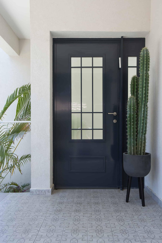 דלת כניסה מברזל כחול כהה עם מרצפות מצוירות בצבעי אפור